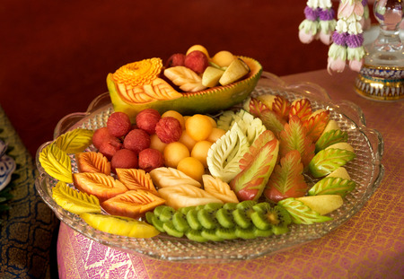 Popular in Thailand mixed Thai fruit as dessert dish after meal with Thai fruit carving style placed on Thai silk decoration