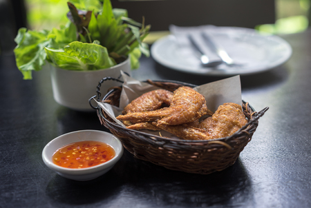 Fried chicken wings in basket or in bowl, and sweet and sour sauce with chili  for chicken dip, by selective focus