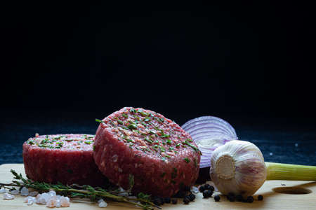 raw organic beaf steak tartare burger patty with onion,garlic,thyme,pepper and himalayan crystal salt