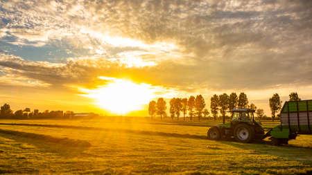 landbouwveld bij zonsopgang met landbouwtractorvrachtwagen Stockfoto