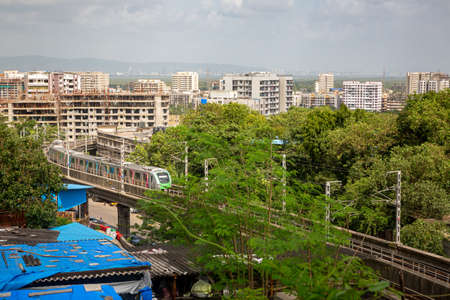 Suburban mumbai city aerial view with metro rail line between slums and buildings Stok Fotoğraf