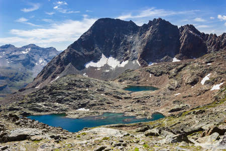 Hiking in Aosta valley, Grauson walloon, Cogne, Italy. View of third lake of Lussert from Laures col (3000 m.). Banque d'images