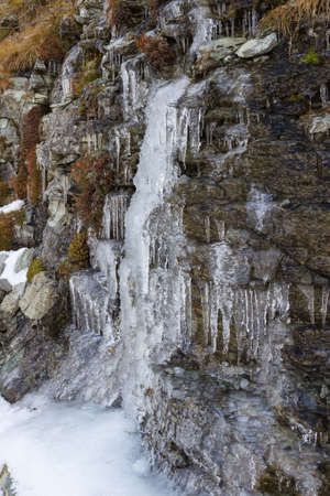 Autumn in the mountains. Icicles on the rocks. Aosta valley, Italy