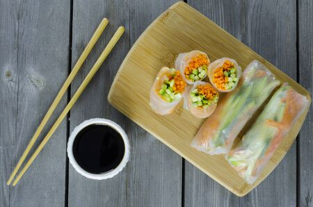Portion of spring rolls on a bamboo board with smoked salmon, caroot and cucumber.