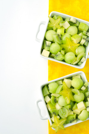 fresh healthy fruit salad and ingredients on yellow background with free space photo