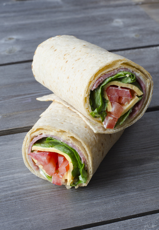 wrap sandwich with salami lettuce tomatoes and cheeses