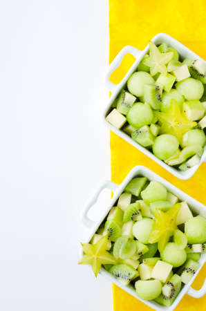 fresh healthy fruit salad and ingredients on white background photo