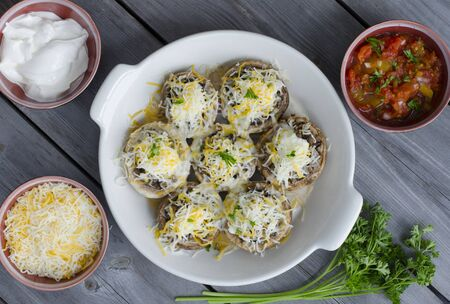 Baked mushroom caps stuffed with fried mushrooms onion cheese and spices. photo