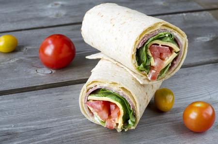 サラミ、レタス、トマト、チーズのサンドイッチをラップします。 写真素材