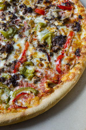 Pizza background. Pizza with meat, bell pepper, onions, cheese and herbs as food background or texture.