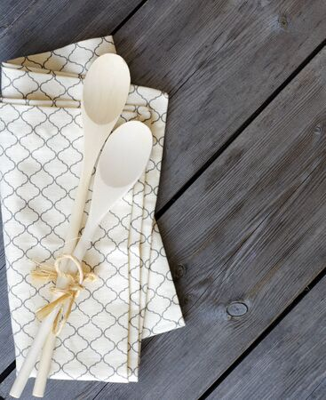 Wooden kitchen spoons on a napkin on a wooden background with copyspace