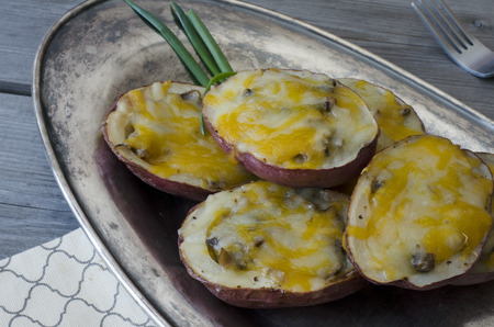 Potato skins. Baked potato halves stuffed with mushrooms, onion and cheese on rustic plate and wooden background. Copy space