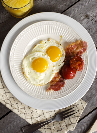 eggs and bacon: Breakfast with fried eggs, bacon, grilled tomatoe and orange juice.