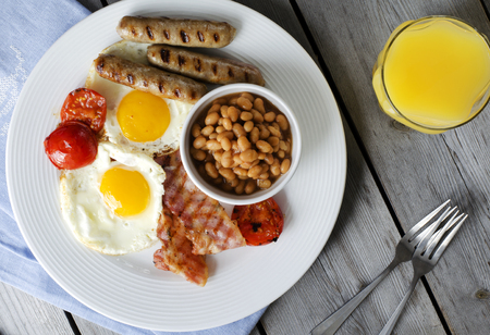 English breakfast or a full English breakfast. Breakfast with fried eggs, bacon, sausages, beans, grilled tomatoe and orange juice. Stock Photo