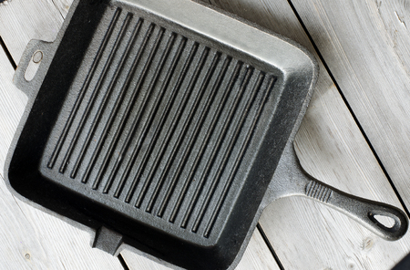 cast iron: Cast iron griddle pan on wooden background