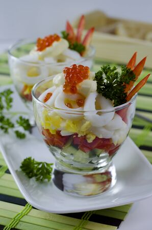 Delicious seafood salad in a glass with calamari, cucumber, eggs, bell pepper and red caviar