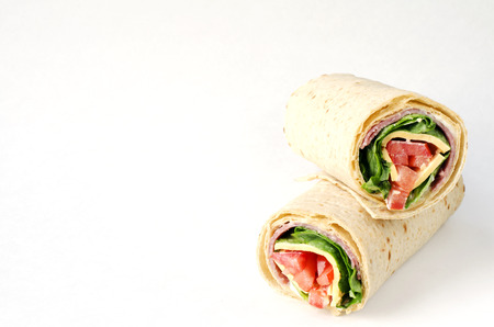 tortilla wrap: wrap sandwich with salami, lettuce, tomatoes and cheeses on white background with copy space. Stock Photo