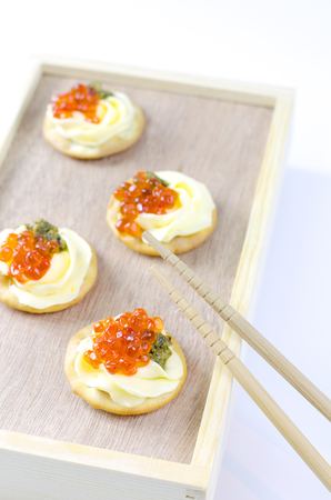 Caviar appetizers with pesto cream cheese and crackers Stock Photo