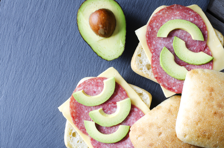 Italian ciabatta sandwich with salami, cheese and avocado on wooden background Фото со стока