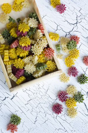 rotini: five color flower pasta on white cracked background as texture or background