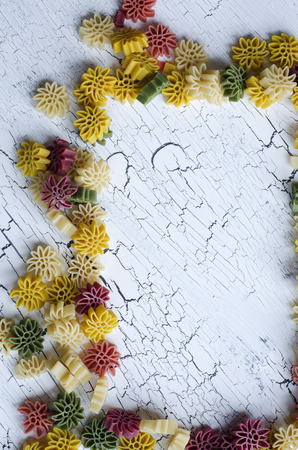 rotini: Decorative frame of five color flower pasta on white cracked background as texture or background