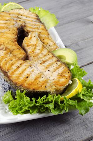 meat and alternatives: Freshly fried salmon steak with lettuce and lemon