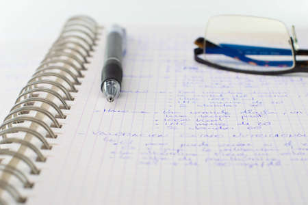Metallic spiral notebook, with a pen and glasses on it