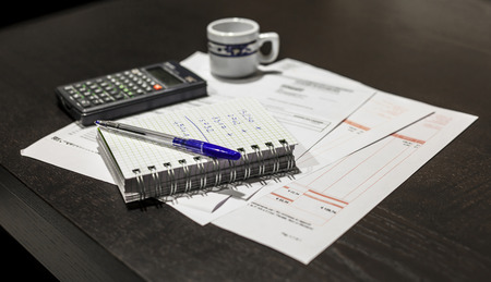 Cálculo de la escena facturas de servicios públicos con la pluma, las facturas, la calculadora y el café