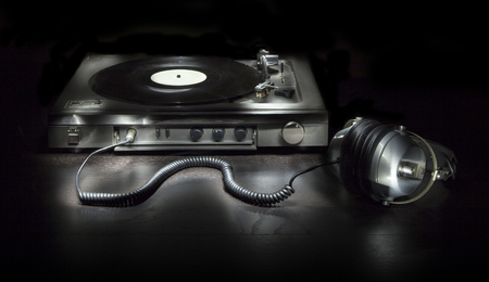 phono: Old turntable with headphones isolated on a black background Stock Photo