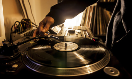 Dj in studio puts needle on record photo