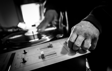 phono: Dj in studio uses turntable and mixer for scratching  Black and white image Stock Photo