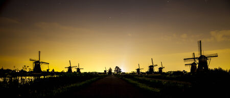 Picturesque landscape with windmills at sunset photo