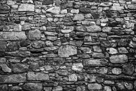 brick mason: Texture of an old wall with different size stones. Black and white image  Stock Photo