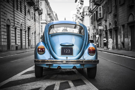 historic and vintage: Old blue car in a black and white city  Stock Photo