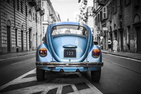 Oude blauwe auto in een zwart-witte stad