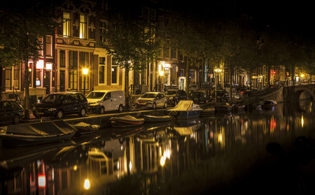 nocturnal: Romantic nocturnal view of Amsterdam: canal in the Red District. Buildings, cars and boats are reflected in the water