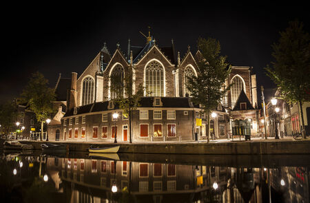 nocturnal: Romantic nocturnal view of Amsterdam: The Oude Church and canal in the Red District. Church and boats are reflected in the water