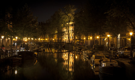 nocturnal: Romantic nocturnal view of Amsterdam: canal in the Red District. Buildings, bridge and boats are reflected in the water. The street lamps form a cross with the illuminated building in the center