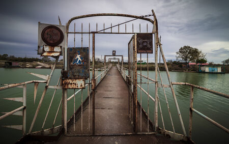 green river: Old metal footbridge and antique gate with rusty signboard. Dark green river in a cloudy day