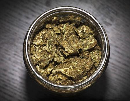 forbidden love: Glass jar full of marijuana on wooden black table