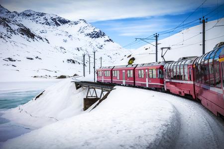 treno espresso: Bernina Express treno, uno dei più alti ferroviaria del mondo, attraversa un piccolo ponte in montagna di neve vicino a un lago ghiacciato
