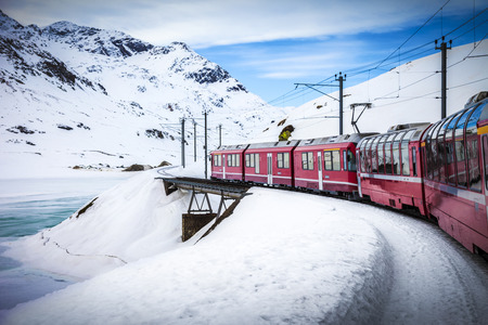 Bernina Express train, one of the highest railway in the world, goes across a little bridge in snowy mountain near a frozen lake