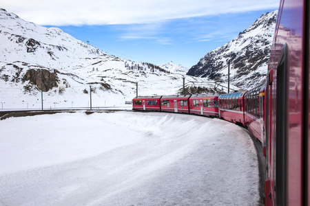 Bernina Express train, one of the highest railway in the world, goes across snowy mountain between Italy and Switzerland Editöryel