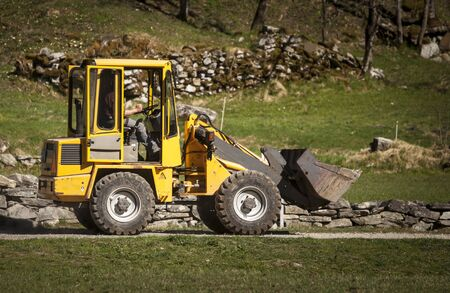 stone cutter: Man drives a yellow backhoe loader in a country road