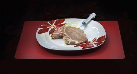 genetically modified organism: Concept genetically modified organism: syringe and raw meat on a dish isolated on a black background