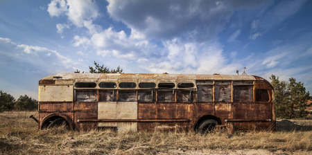 pripyat: Abandoned and rusty bus in a field in a sunny day with blue sky and clouds in the Chernobyl nuclear power plant zone of alienation