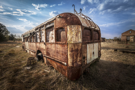 alienation: Abandoned and rusty bus in a field in a sunny day with blue sky and clouds in the Chernobyl nuclear power plant zone of alienation