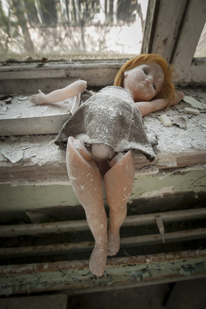 alienation: Old bent doll placed near a window in an abandoned kindergarten in Pripyat - Chernobyl nuclear power plant zone of alienation Stock Photo