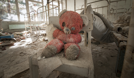 pripyat: Old red teddy bear sitting on a chair in an abandoned kindergarten in Pripyat - Chernobyl nuclear power plant zone of alienation