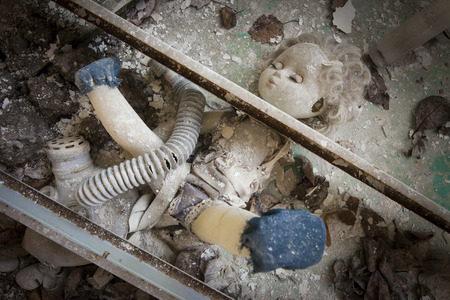 alienation: Old doll placed under two metal beams in an abandoned kindergarten in Pripyat - Chernobyl nuclear power plant zone of alienation. One of this metal beams seems beheading the doll Stock Photo